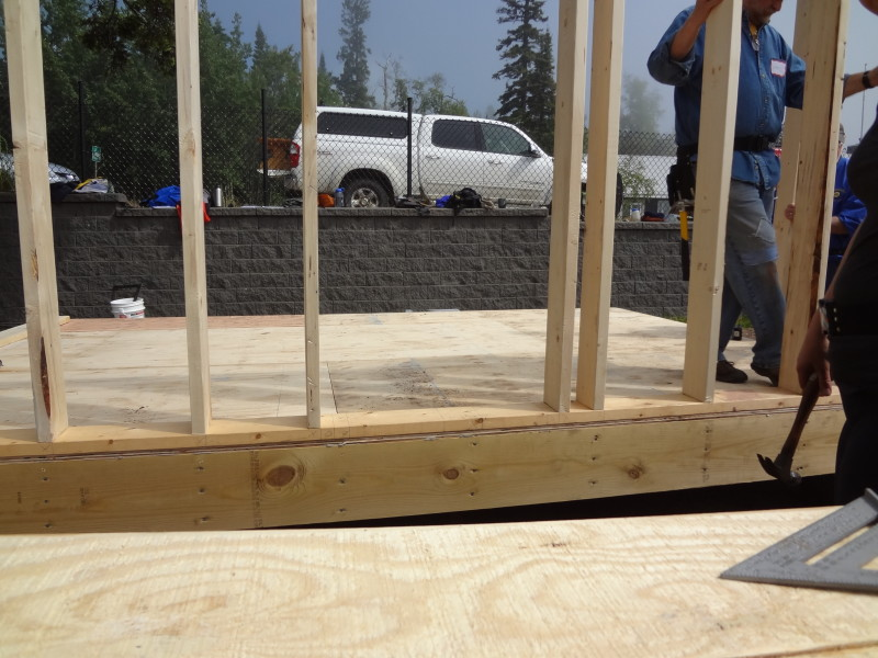 Notice how studs are aligned with floor joists (vertical rows of nails along rim joist). The two studs that are not aligned with floor joists are for framing the window.
