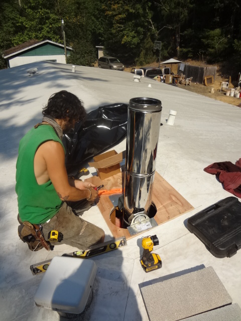 "Working on the chimney pipe on the roof. Note: 2"" minimum space all around the chimney."