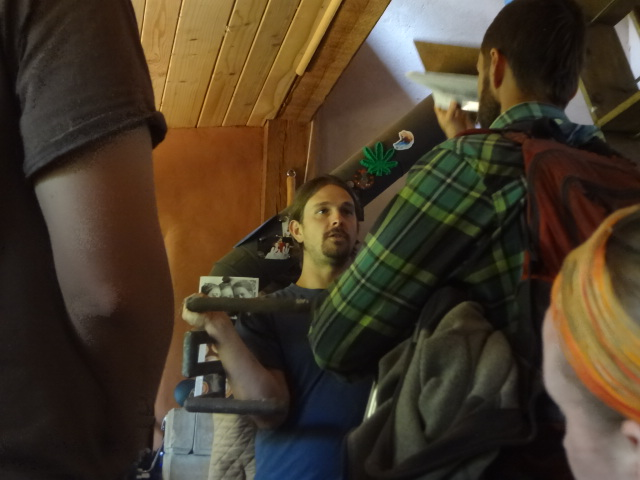 Chris is holding a pipe that fits into the stove and can heat water when the stove is used.
