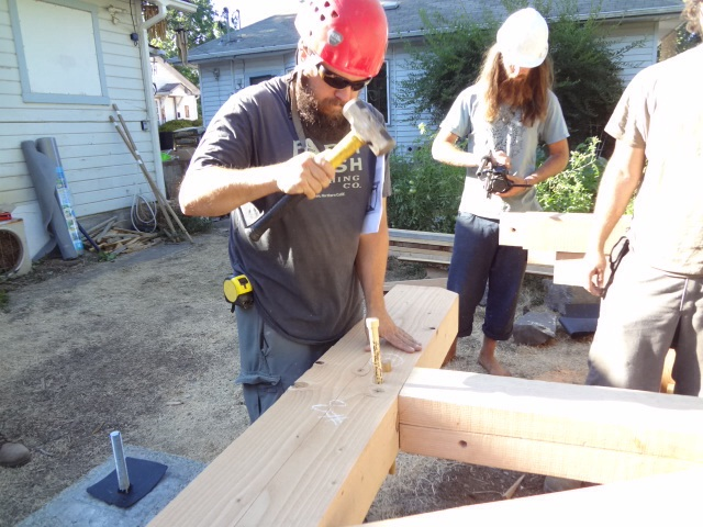 Assembling the first wall on site. Driving the pegs through the pre-drilled holes.