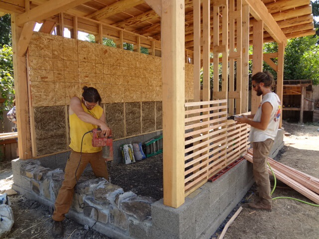 As wood lath gets attached to the front wall, Chris drills holes for threaded posts to be placed in the rock wall.